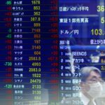 FILE PHOTO: A passersby wearing a protective face mask is reflected on screen displaying the Japanese yen exchange rate against the U.S. dollar and stock prices at a brokerage, amid the coronavirus disease (COVID-19) outbreak, in Tokyo